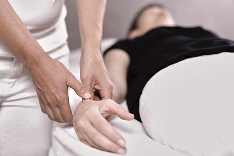 An einer Frau werden Akupressur und Akupunkt-Massage angewendet
