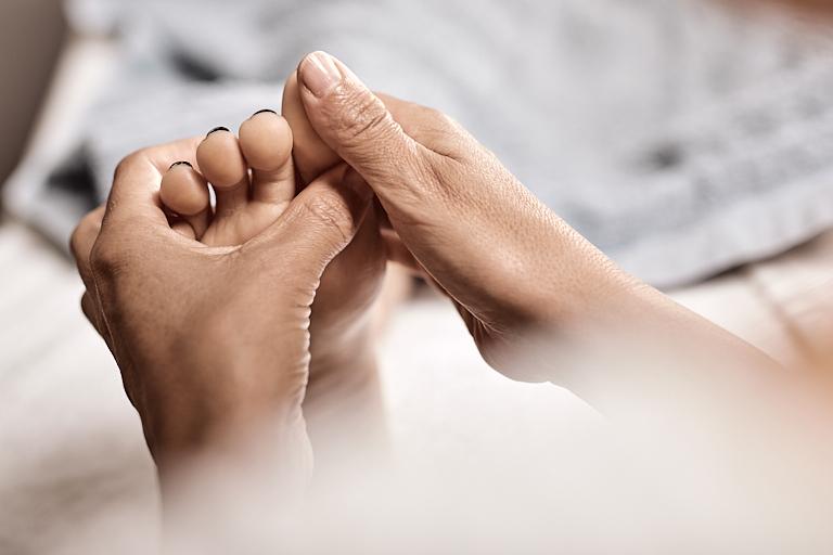 Massagetherapeutin massiert die Reflexzonen eines Fusses
