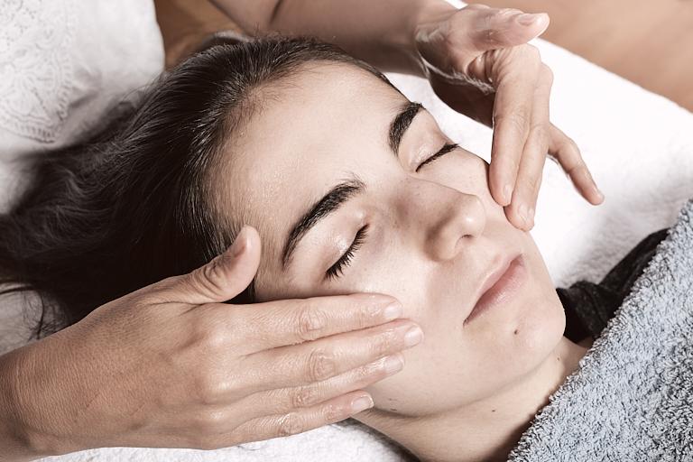 Massagetherapie: Therapeutin massiert das Gesicht einer entspannt liegenden Frau