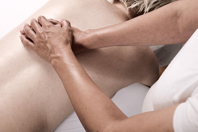Massagetherapeutin massiert den Rücken einer Frau