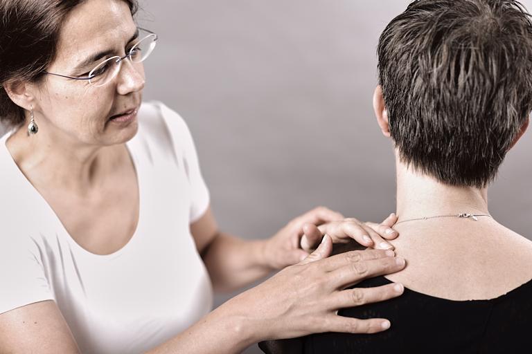 Massagetherapeutin untersucht Verspannungen an der Schulter